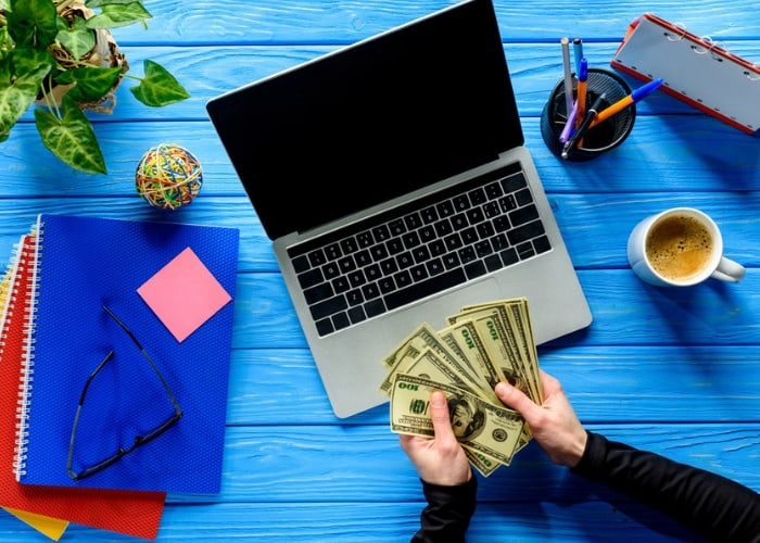 Laptop on table with cash (freelance writing)